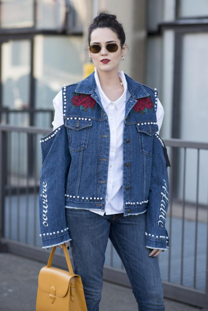 Milan Fashion Week Fall: Auf den Straßen zeigt sich eine Frau mit Cold-Shoulder, Perlenverzierung und Patches auf ihrer Jeansjacke während der Show von Antonio Marras