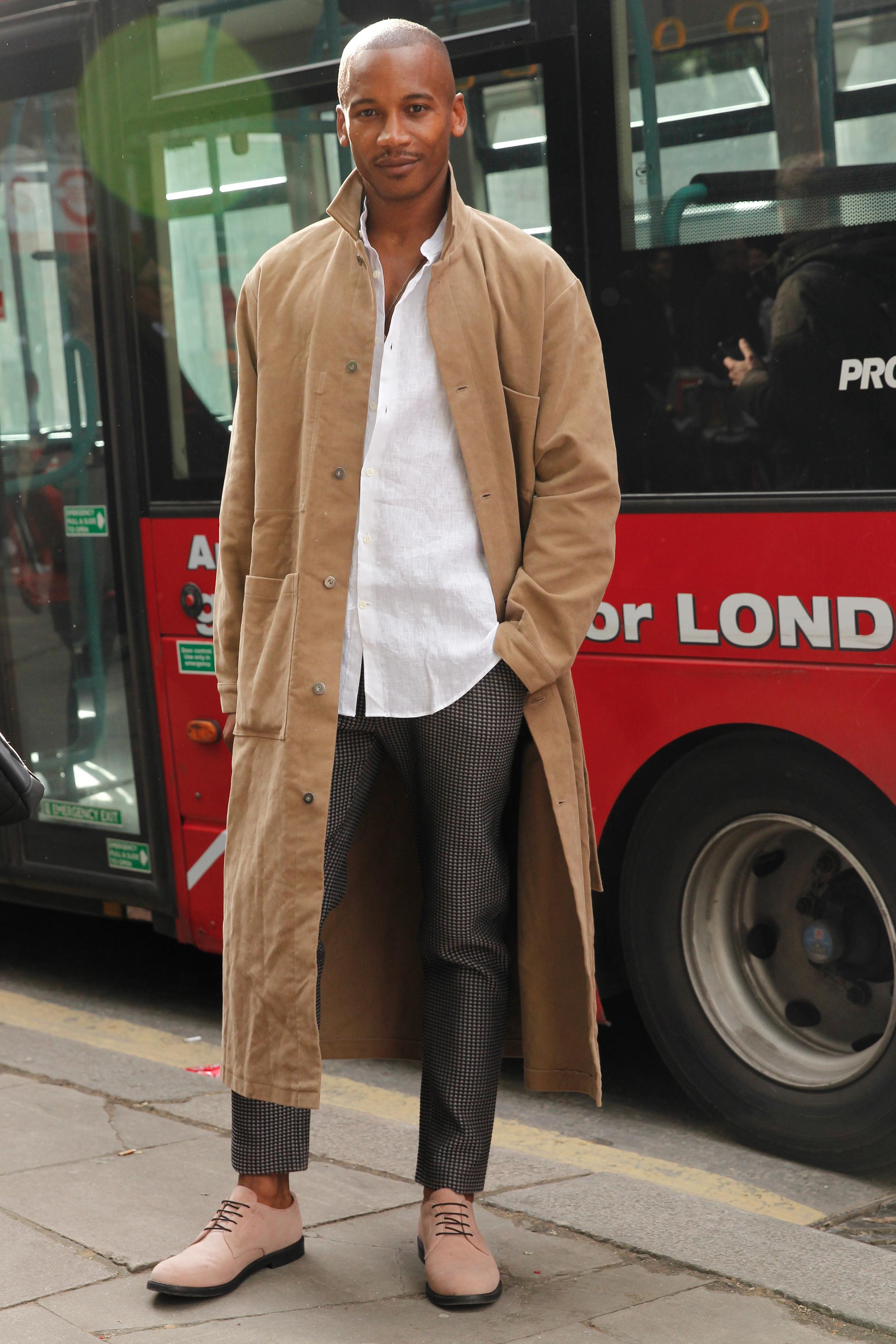 Street Style London: Ein Mann trägt zum langen braunen Mantel eine gemusterte Hose und ein einfaches Leinenhemd in Weiß