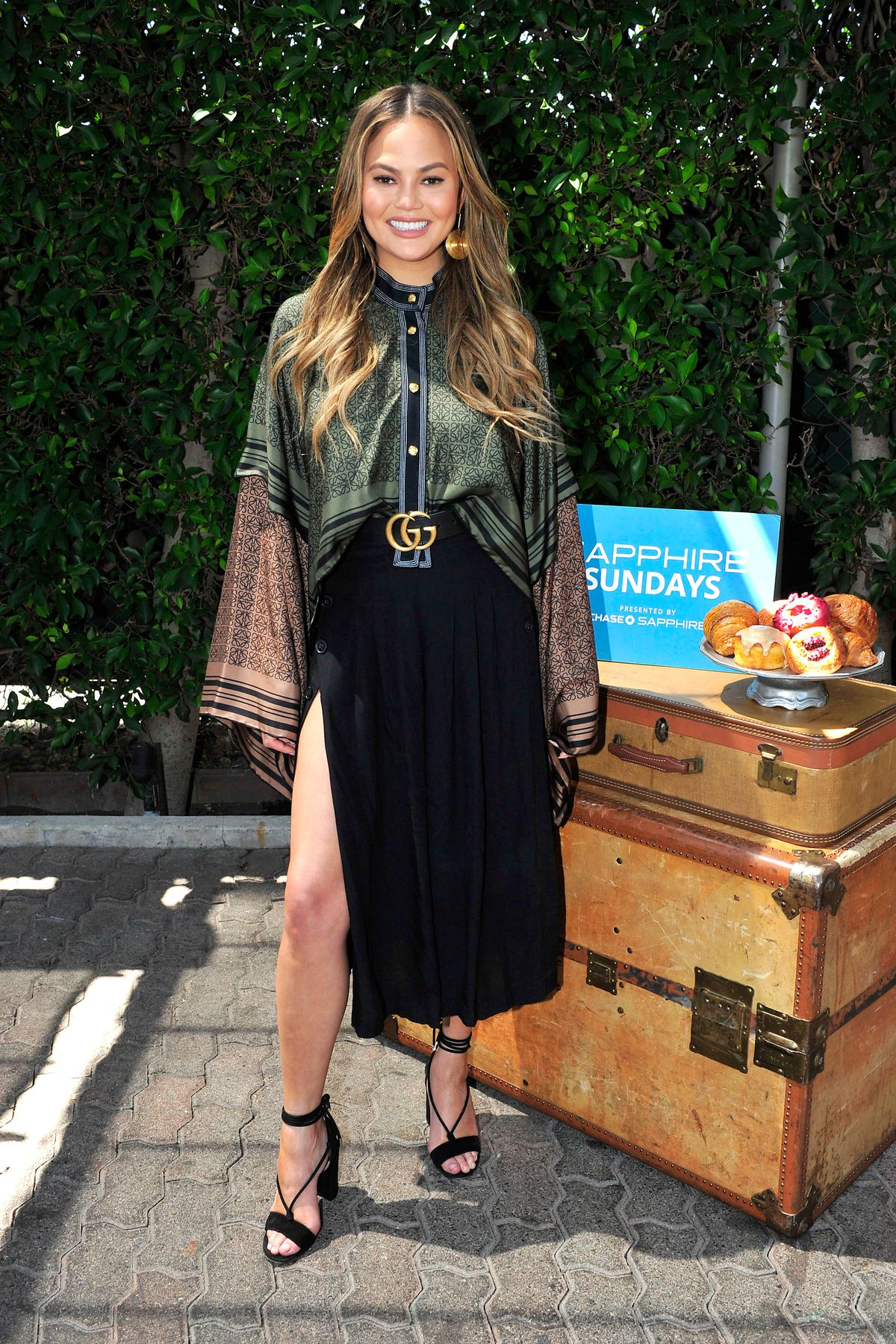 Chrissy Teigen hübscht mit dem Gucci-Gürtel ihr Outfit auf