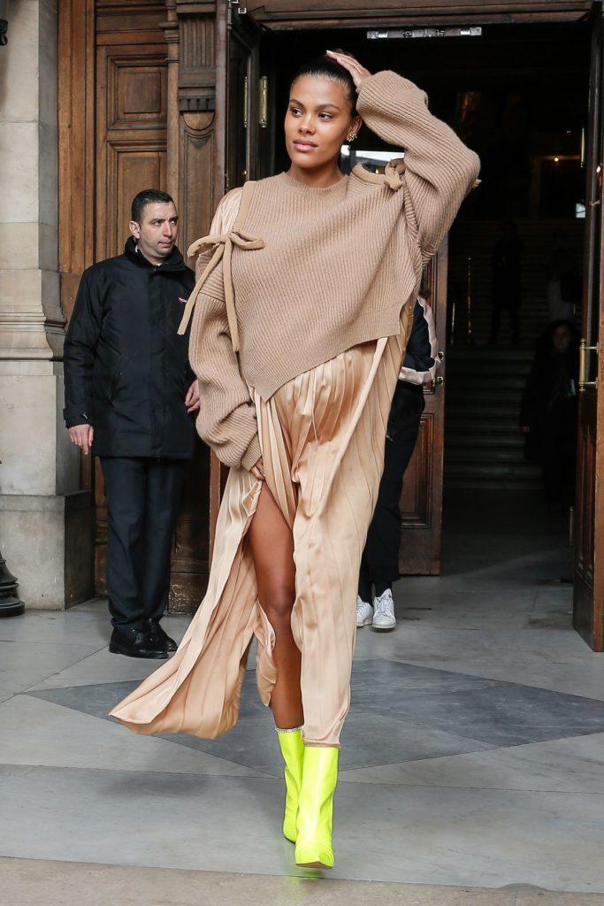 Model Tina Kunakey kombiniert neongelbe Stiefeletten zu gedeckten Farbtönen (ddp images)