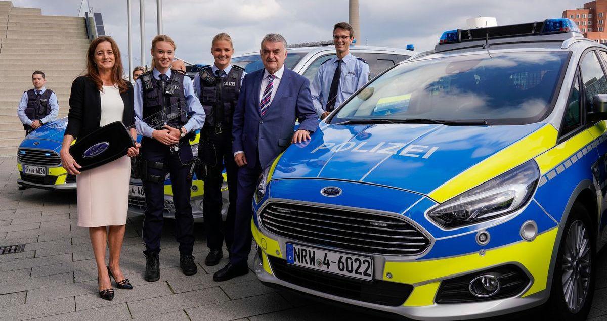 Claudia Vogt (l.), Direktorin Gewerbe- und Großkundengeschäft der Ford-Werke, übergibt Nordrhein-Westfalens Innenminister Herbert Reul (2.v.r.) symbolisch den Schlüssel für einen Ford S-Max Streifenwagen.