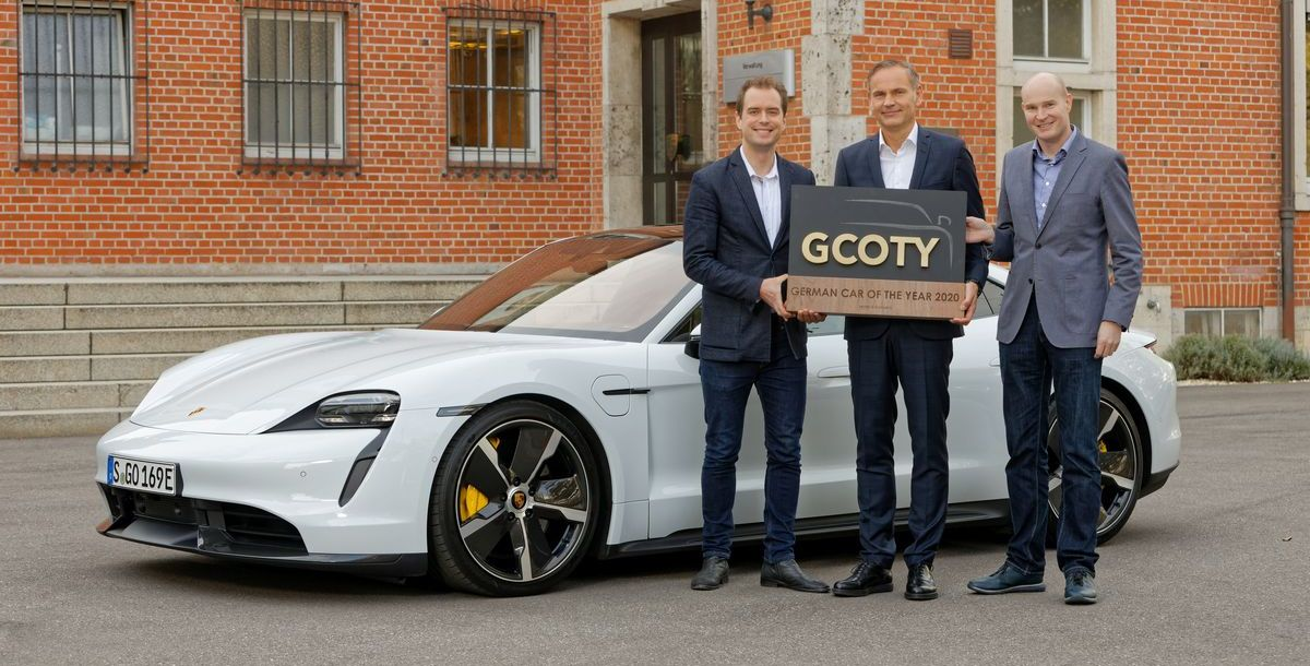 Porsche-Chef Oliver Blume bei der Übergabe der Auszeichnung in Zuffenhausen, umrahmt von Bern Hitzemann (Prime Research, links) und Jens Meiners (German Car of the Year)