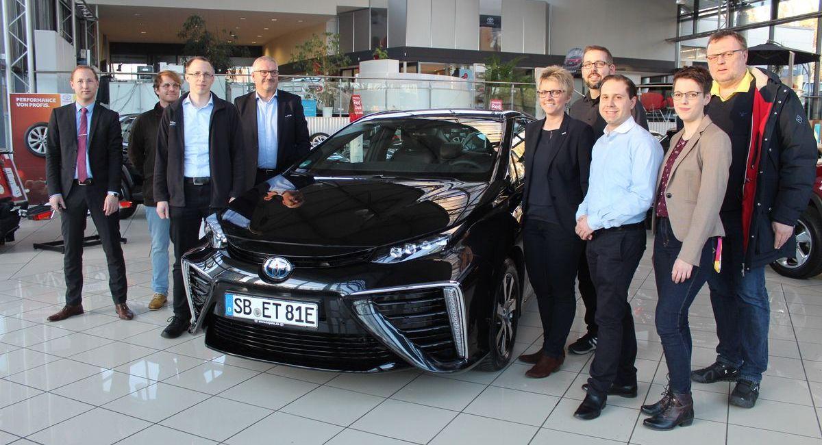 Eine Delegation der Forschungsgruppe Verkehrstelematik (FGVT) der Fakultät für Ingenieurswissenschaften an der Hochschule für Technik und Wirtschaft des Saarlandes holt den Toyota Mirai bei der Autowelt Saarbrücken ab.